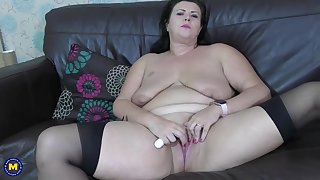 Fat brunette on touching saggy tits is wearing black stockings while masturbating like crazy, on be passed on sofa